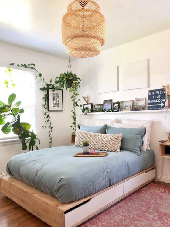 kleines Schlafzimmer schönes Raumdesign Bett aus Holz Schubladen gute Stauraummöglichkeit blaue Bettwäsche sehr einladend wirken