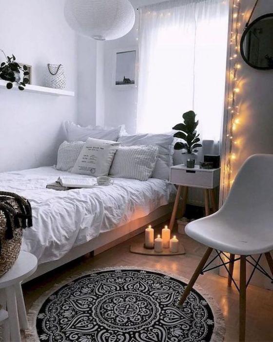 kleines Schlafzimmer schönes Raumdesign Lichterketten an der Wand Kerzen vor dem Bett romantische Atmosphäre