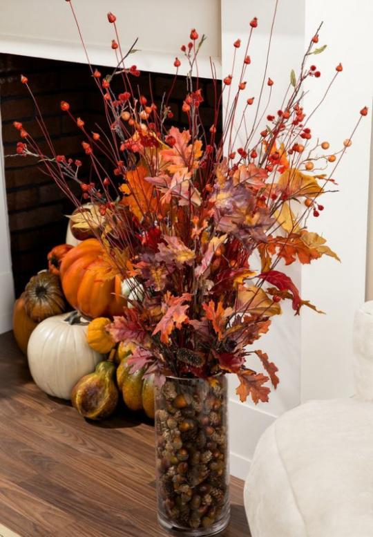 Deko Ideen mit Herbstblättern Glas mit bunten Blättern Kürbisse im Hintergrund