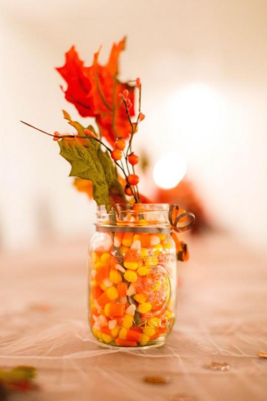 Deko Ideen mit Herbstblättern Glas voll mit Maiskörnern Zweig Beeren zwei bunte Blätter