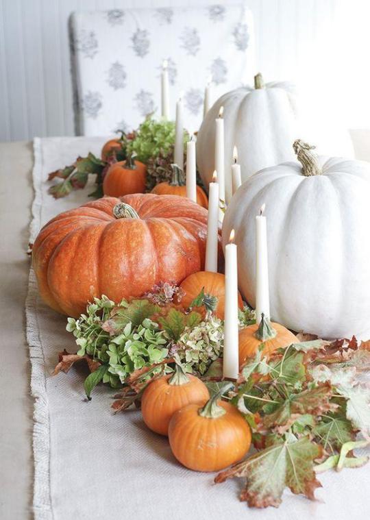 Deko Ideen mit Herbstblättern Tisch gedeckt und dekoriert mit weißen und orangenen Kürbissen