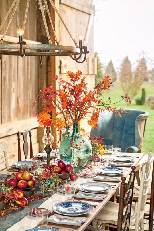 Deko Ideen mit Herbstblättern festlich gedeckter Tisch draußen Vase mit bunten Blättern Blickfang rote Äpfel Beeren