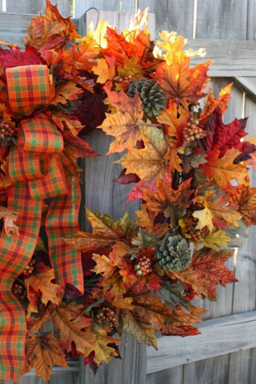 Herbstdeko mit Tannenzapfen Herbstkranz bunte Herbstblätter Schleife am Gartenzaun gehängt
