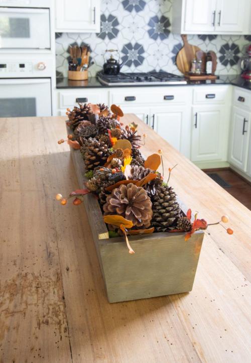 Herbstdeko mit Tannenzapfen Holzkasten in der Tischmitte voll mit Zapfen Herbstblätter Waldbeeren