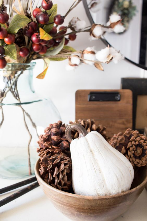 Herbstdeko mit Tannenzapfen Holzschüssel weißer Zierkürbis Zapfen Blickfang daneben Vase mit roten Beeren Zweige