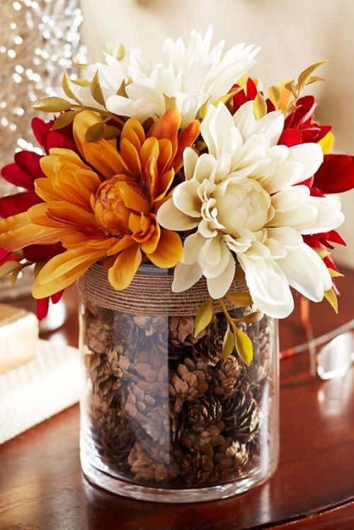 Herbstdeko mit Tannenzapfen großes Glas als Mittelstück auf dem Tisch gefüllt mit Kiefernzapfen mit Herbstblumen Chrysanthemen verziert
