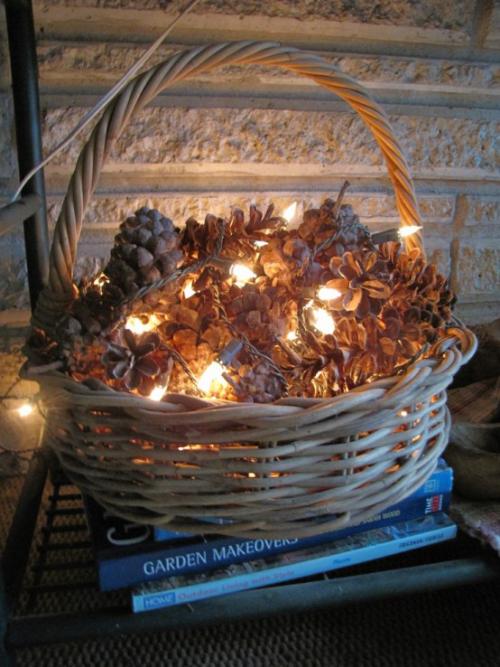 Herbstdeko mit Tannenzapfen in einem Korb auf dem Boden mit Lichterkette Bastelidee für Romantiker