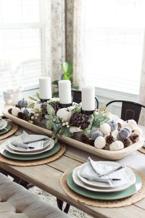 Herbstdeko mit Tannenzapfen weiße Kerzen Zapfen Blätter in einer Holzschale in der Tischmitte festlich gedeckter Tisch