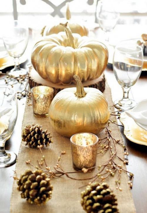 Herbstdeko mit Tannenzapfenzapfen Zierkürbisse im Goldglanz festlich gedeckter Tisch