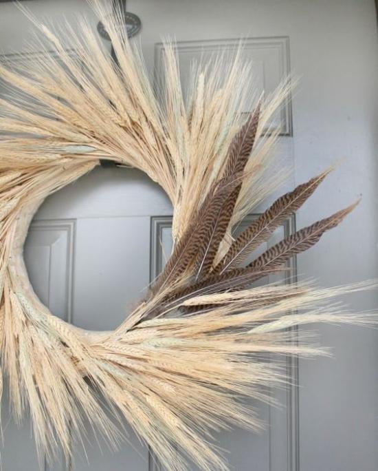 Herbstdeko mit Weizen Türkranz mit Weizenstängeln mit Federn geschmückt
