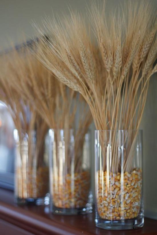 Φθινοπωρινή διακόσμηση με σιτάρι τρία γυάλινα αγγεία γεμάτα με πυρήνες καλαμποκιού που είναι τοποθετημένα σε αυτά Mantelpiece