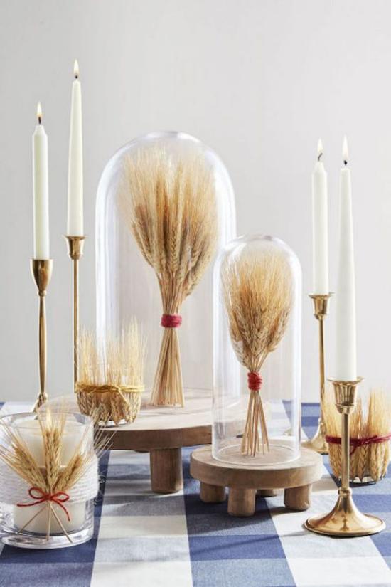 Φθινοπωρινή διακόσμηση με όμορφη διακόσμηση από σιτάρι Δέσμες σιταριού κάτω από γυάλινα κομψά κηροπήγια λευκά κεριά