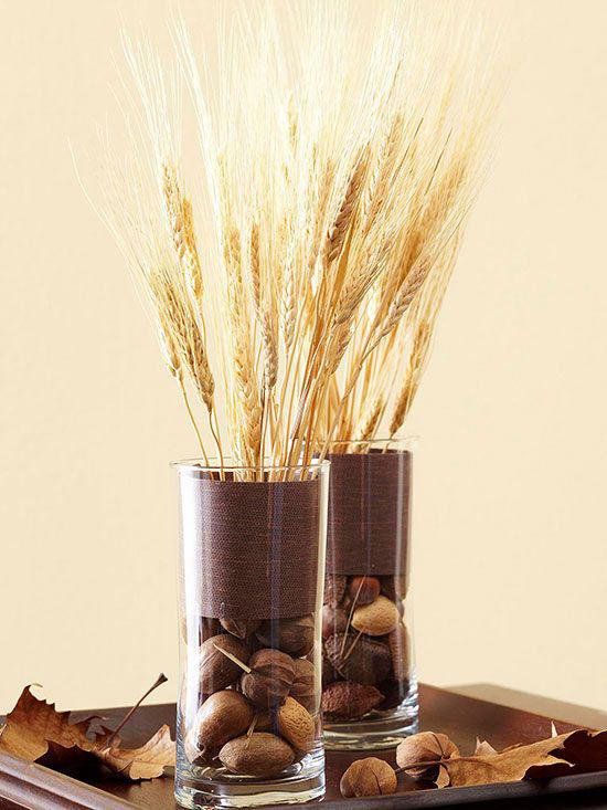 Φθινοπωρινή διακόσμηση με σιτάρι δύο κομψά αγγεία κατασκευασμένα από γυάλινα μίσχους σιταριού καρύδια φθινοπωρινά φύλλα σε ξύλινο δίσκο