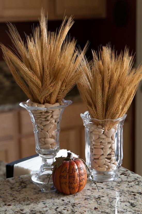 Φθινοπωρινή διακόσμηση με σιτάρι δύο ψηλά γυάλινα αγγεία γεμάτα με φασόλια σε αυτά Μίσχοι σιταριού Κολοκύθα τοποθετημένη στο τραπέζι