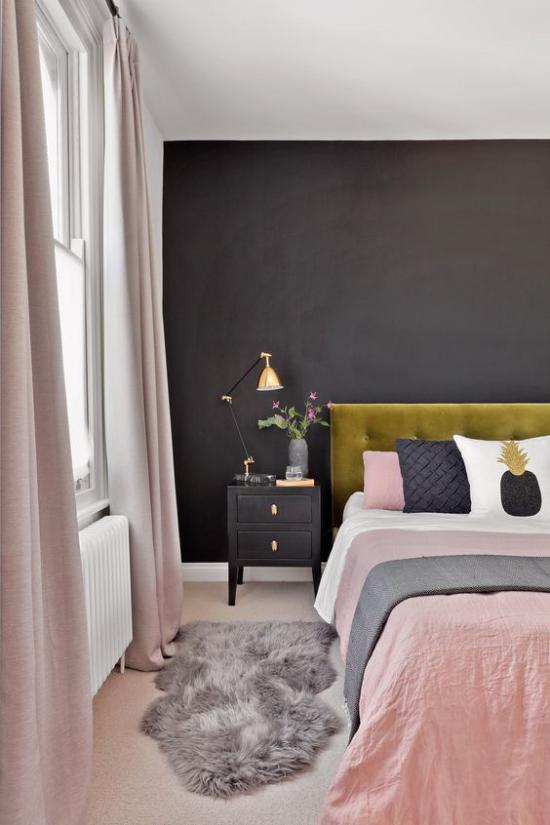 Schlafzimmer Ideen in Schwarz und Rosa helles Interieur schwarze Wand grasgrünes Bettkopfteil Bettwäsche rosa weiß grau kleiner Teppich aus Kunstpelz