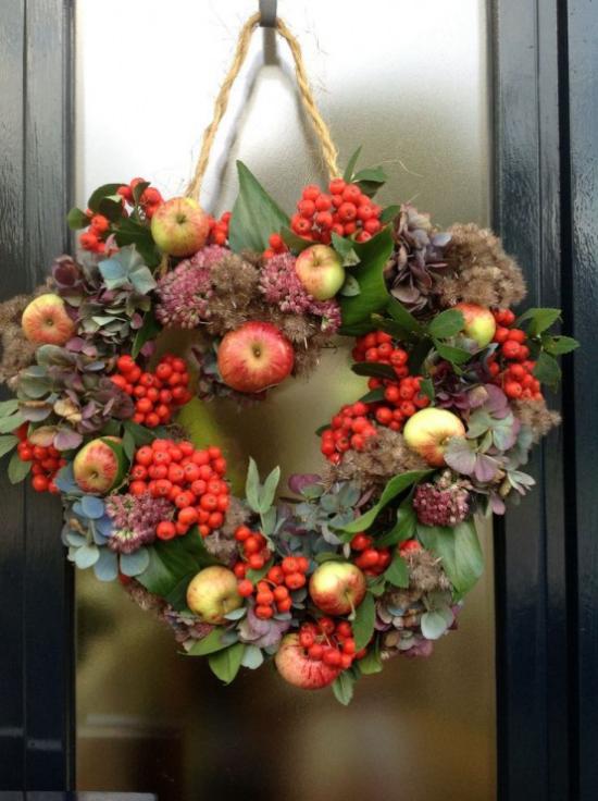Türkranz mit Äpfeln basteln in Herzform an der Eingangstür rote Hagebutten viel Grün