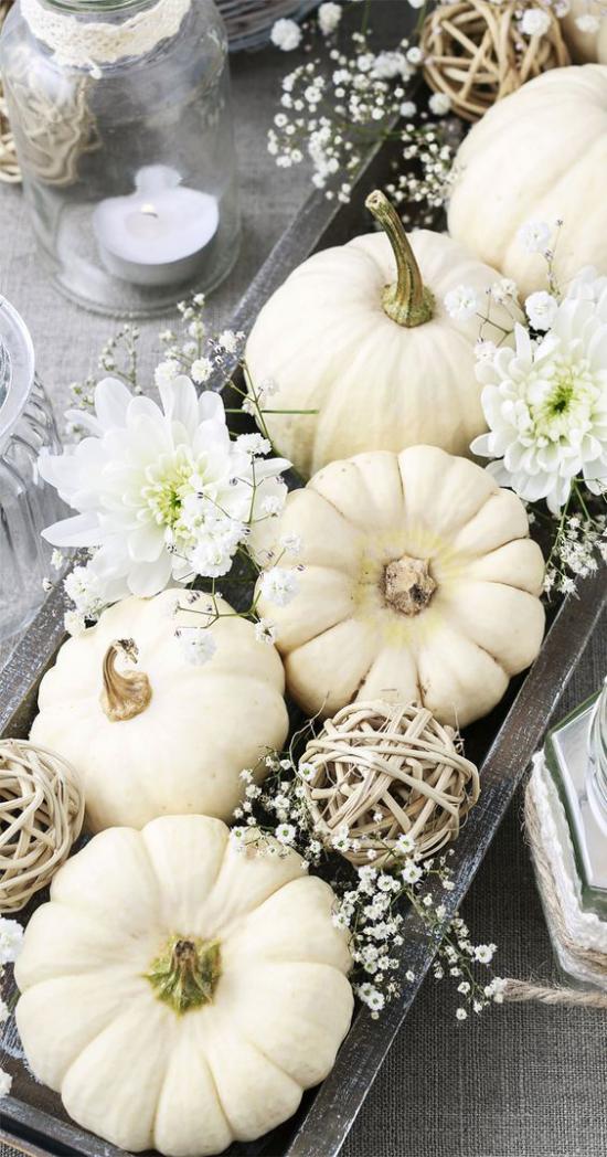 Weiße Kürbisse herbstliche Tischdeko auf einem Tablett in der Mitte mit weißen Blüten verziert
