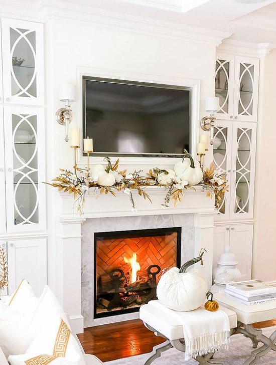 Weiße Kürbisse herbstliche Tischdeko brennendes Feuer im Kamin Kaminsims dekoriert großer Kürbis auf dem Tisch vor dem Kamin