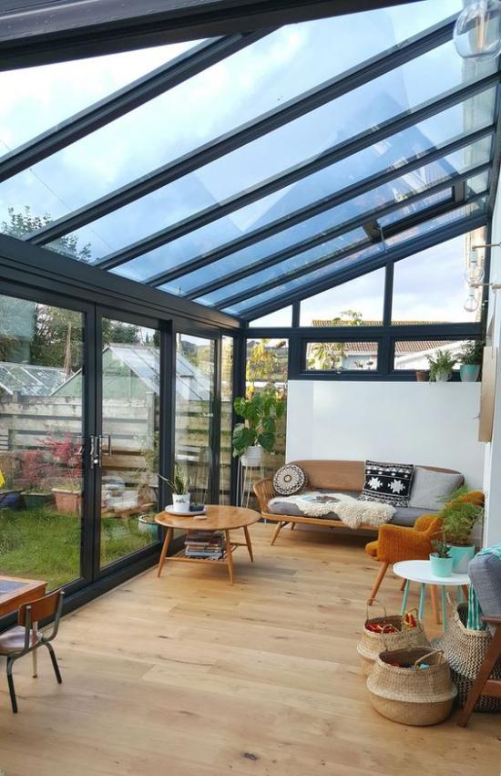 Χειμερινός κήπος για αγκαλιά απλή επίπλωση παλιά έπιπλα καναπέ στρογγυλό τραπέζι πολυθρόνα ψάθινα καλάθια