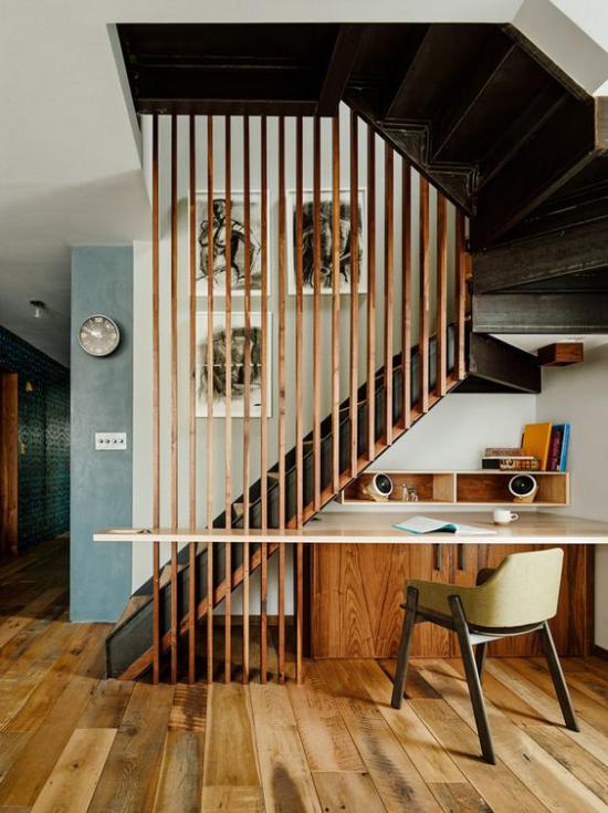 Arbeitsecke unter der Treppe sehr stilvolle Gestaltung viel Holz warme Farben praktischer Schreibtisch bequemer Stuhl