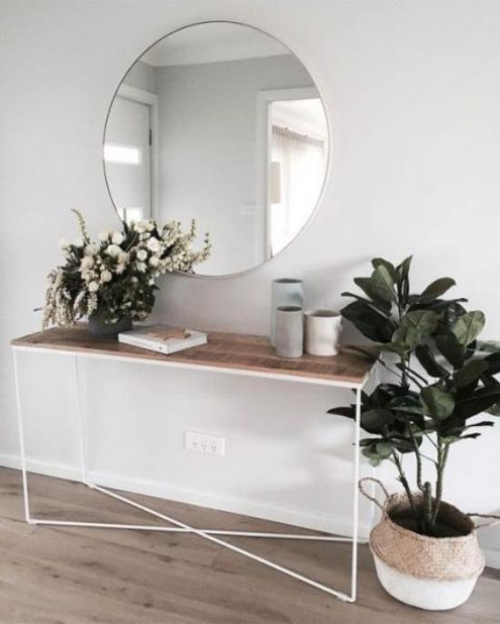 Eingangsbereich einfacher Konsolentisch runder Spiegel grüne Topfpflanze grüne Zweige in Vase modern und einladend gestalten