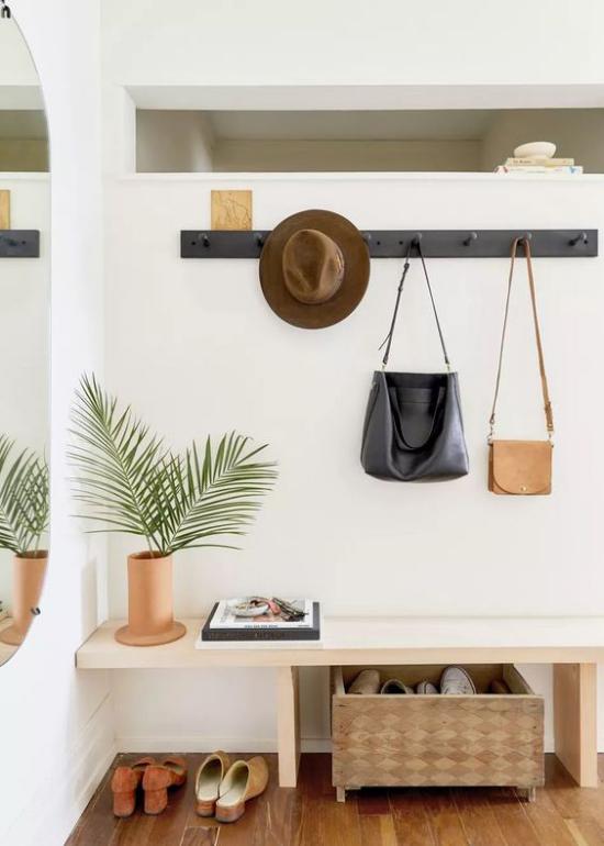 Eingangsbereich modern gestalten Taschen an der Wand hängen Hut Schuhe unter der Sitzbank