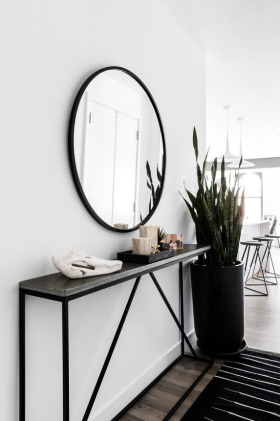 Eingangsbereich modern gestalten Weiß und Schwarz im Kontrast runder Wandspiegel hohe Topfpflanze