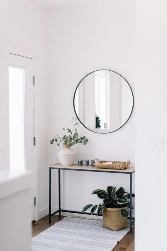 Eingangsbereich modern gestalten einfache Flurmöbel Tisch Grünpflanze weiße Vase mit grünen Zweigen heller Teppich runder Spiegel