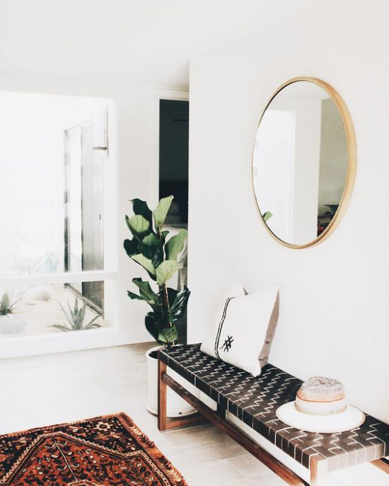 Eingangsbereich modern gestalten mit Boho Stil Elementen bunter Teppich Grünpflanzen runder Spiegel Sitzbank