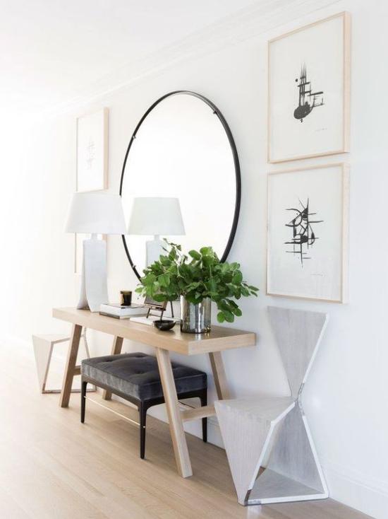 Eingangsbereich modern gestalten runder Spiegel weiße Tischlampe einfache Möbelstücke Wandbilder