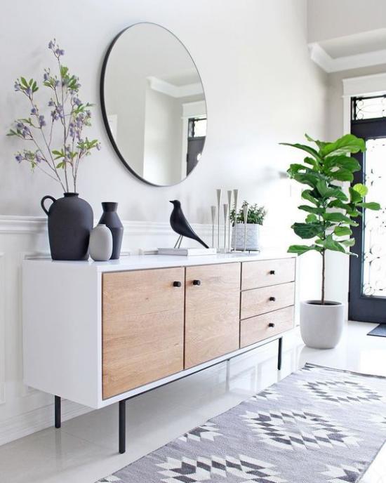 Eingangsbereich modern gestalten sehr einladen Tür mit Glasscheibe Licht Teppich eine grüne Topfpflanze Deko Artikel