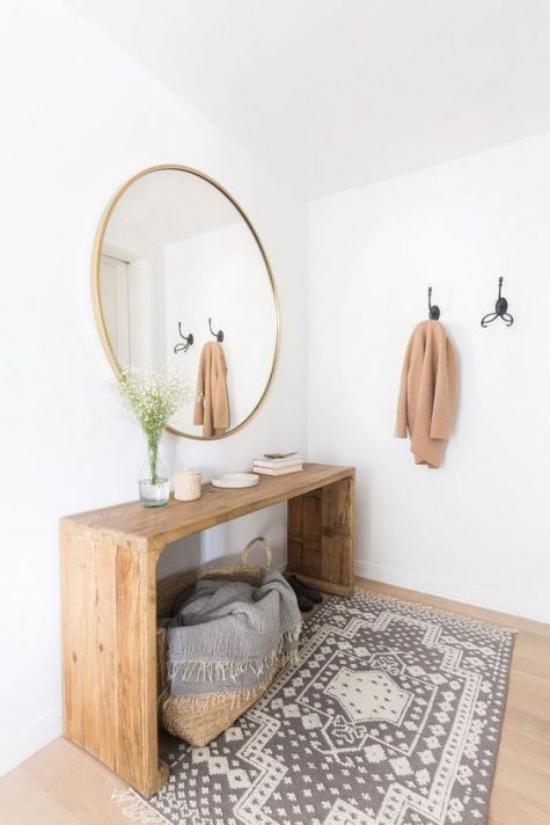 Eingangsbereich modern gestalten simpel einfache Einrichtung wenig Möbel runder Wandspiegel Holzboden Teppich
