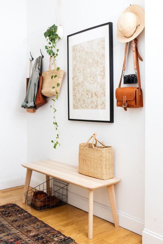 Eingangsbereich modern gestalten wenig Möbel Taschen Hut an Haken Korbtasche