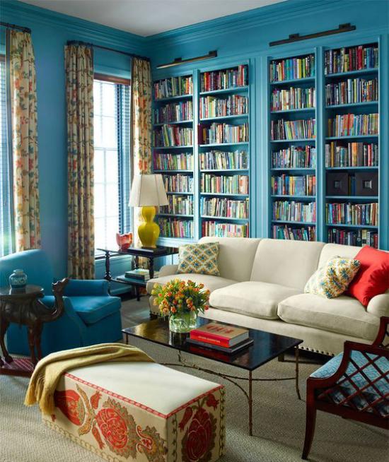 Eingebaute Bücherregale Wohnzimmer klassisches Raumdesign Blau dominiert Sessel helles Sofa Hocker Lampe gelbe Gardinen