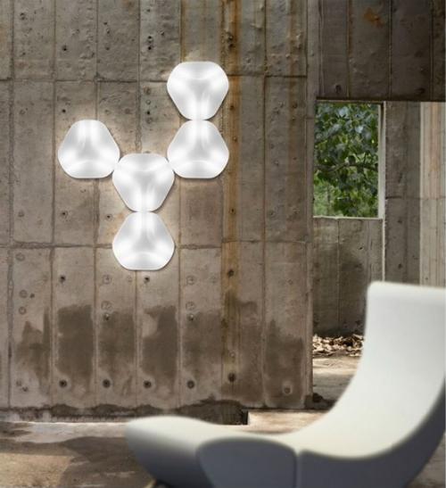 Extravagante Wandleuchten Industrial Style grobe graue Betonwand fünf Lampen gruppiert geometrische Form schicker Sessel im Vordergrund