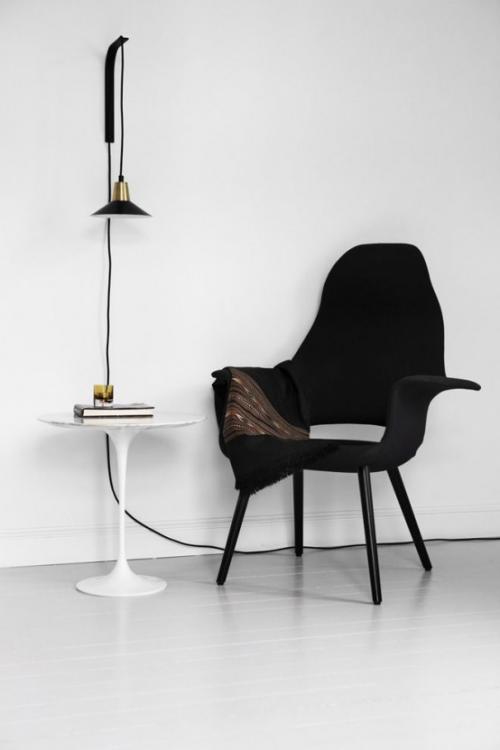 Extravagante Wandleuchten raffiniert auffallend in Industrial Style auf weißem rundem Tisch daneben schwarzer Sessel