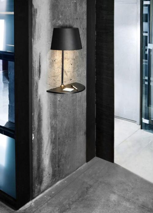 Extravagante Wandleuchten schwarze Wandlampe aus Metall grobe graue Betonwand im Industrial Style im Flur