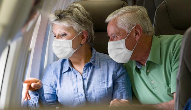 Fliegen während Corona Ansteckungsgefahr für ältere Leute höher Mann Frau über 65 im Flugzeug
