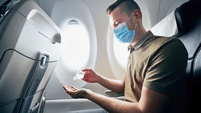 Fliegen während Corona Passagier im Flugzeug Desinfektionsmittel benutzen Hände desinfizieren