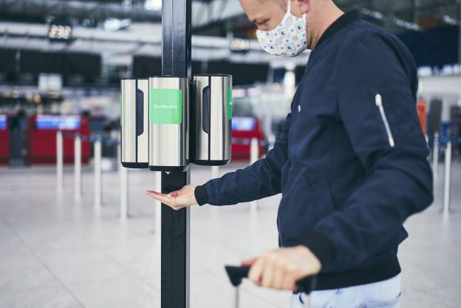 Fliegen während Corona am Flughafen Hände desinfizieren