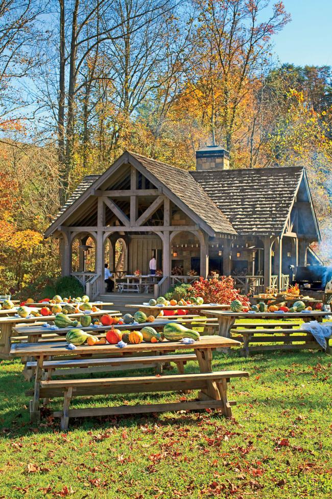Herbstdeko für draußen Herbstparty im Garten Holztische Sitzbänke viele Kürbisse kleines Haus im Hintergrund