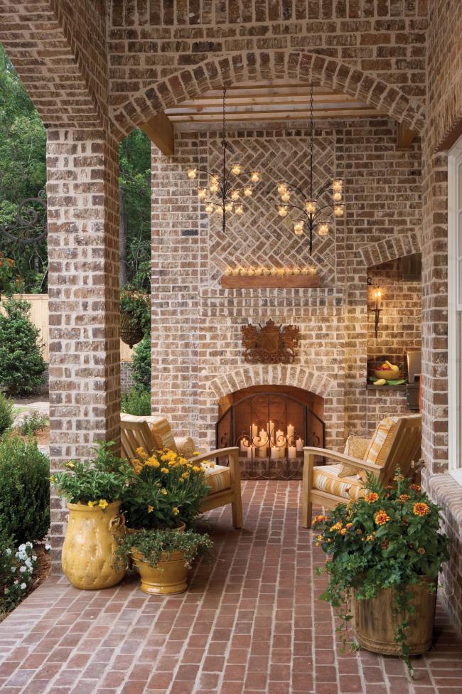 Herbstdeko für draußen Sitzecke auf der Veranda für zwei passende Beleuchtung viele weiße Kerzen Blumenbehälter Herbstblumen