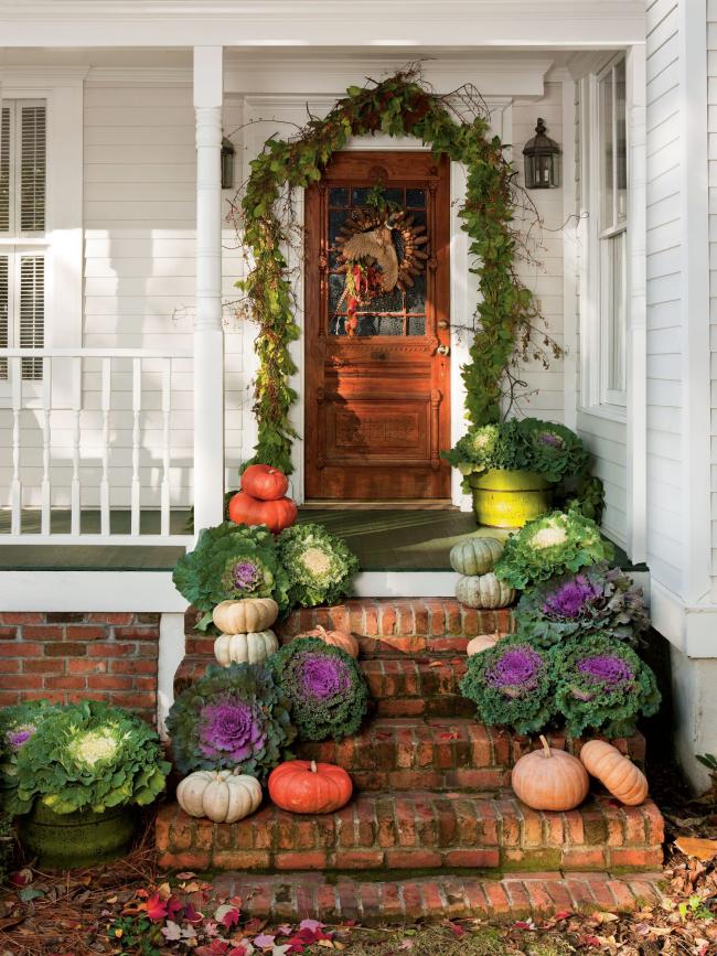 Herbstdeko für draußen Zierkraut Kürbisse auf den Treppen vor der Haustür arrangiert