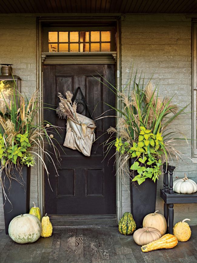 Herbstdeko für draußen im rustikalen Stil Beutel mit getrockneten Gräsern dunkle Tür zwei hohen Blumenbehälter beiderseits Kürbisse verschiedene Farben und Größen