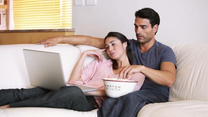 Keine langfristige Beziehung Sternzeichen ein junges Paar verliebt auf der Couch zuhause Laptop zufrieden ausgeglichen