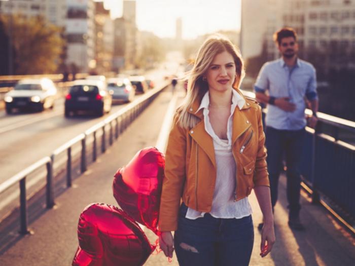 Keine langfristige Beziehung Sternzeichen junge Frau enttäuschtes Gesicht Mann im Hintergrund