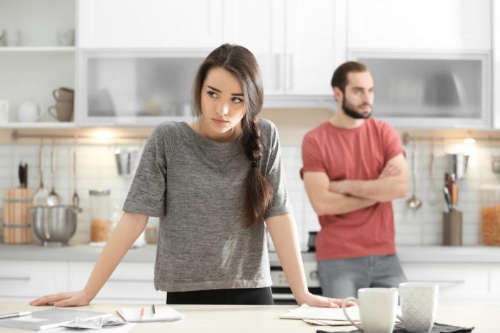 Keine langfristige Beziehung Sternzeichen junges Mädchen Mann im Hintergrund in der Küche Verzweiflung