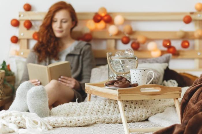 Sternzeichen gern alleine unabhängige Einzelgänger Stier Relax im Bett mit Buch in der Hand Leckereien griffnahe