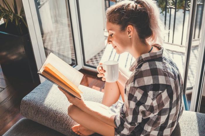 Sternzeichen gern alleine unabhängige Einzelgänger junges Mädchen zu Hause Kaffee trinken ein Buch lesen