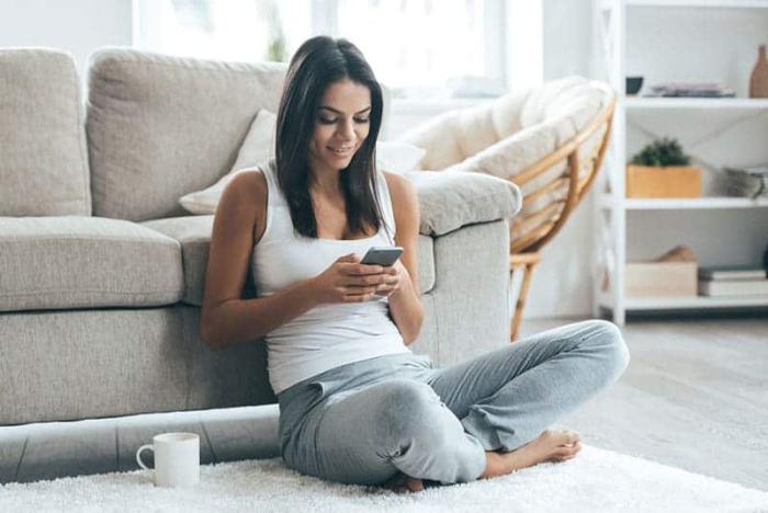 Sternzeichen gern alleine unabhängige Einzelgänger zu Hause junges Mädchen auf dem Boden sitzen per handy kommunizieren